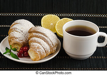fresh cup of hot black coffee with croissants and lemon