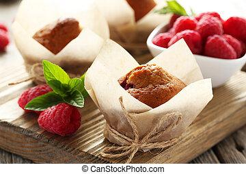 Fresh cupcakes with raspberries on cutting board