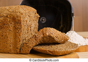 Fresh cutted loaf of rye bread with breadmaker and gluten free flour on wooden table