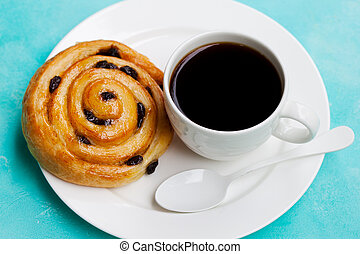 Fresh danish pastry with raisins with a cup of black coffee on blue table background.
