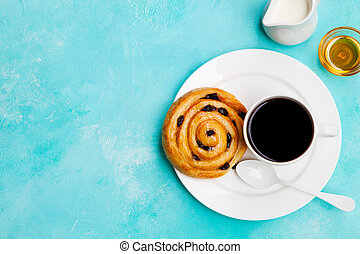 Fresh danish pastry with raisins with a cup of black coffee on blue table background. Top view. Copy space.