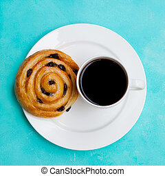 Fresh danish pastry with raisins with a cup of black coffee on blue table background. Top view.