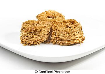 Fresh delicious arabic sweets, kanafeh, on a plate, white background