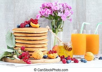 Fresh delicious pancakes with summer berries on light...