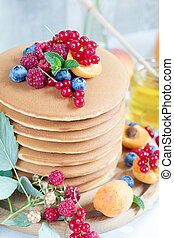 Fresh delicious pancakes with summer berries on light background.