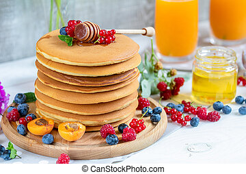 Fresh delicious pancakes with summer berries on light surface