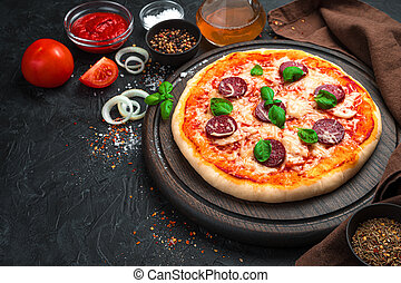 Fresh, delicious pepperoni pizza close-up on a black background. Side view.