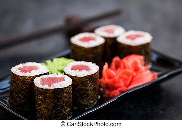 Fresh delicious tuna maki sushi rolls on dark background, ...