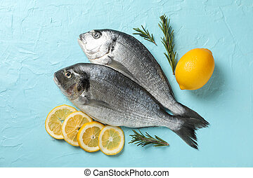 Fresh Dorado fishes, lemon and rosemary on blue background, top view