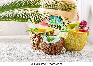 Fresh drinks in fresh fruits with cocktail umbrellas