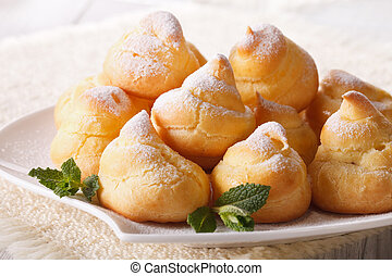 Fresh eclairs with powdered sugar and mint close up. ...