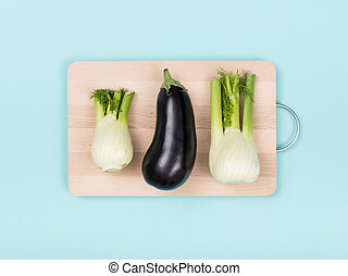 Fresh eggplant and fennels on a chopping board