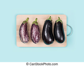 Fresh eggplants on a chopping board
