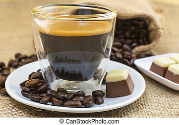 fresh espresso coffee with crema and pralines on plate -...