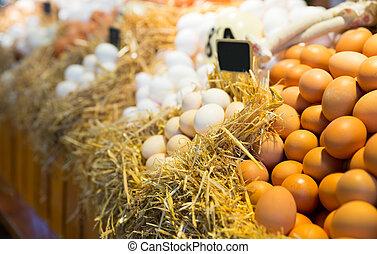 Fresh farm eggs on a straw in market
