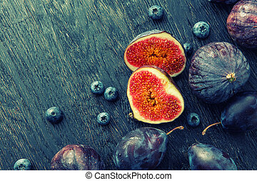 Fresh figs and blueberries, on black background