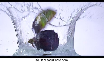 Fresh figs fruits fall into the water. Slow motion.