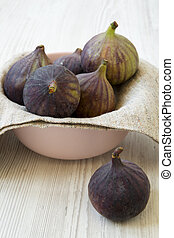 Fresh figs in a pink bowl on a white wooden background, side view. Close-up.