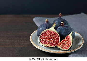 Fresh figs in a white plate on a dark background. Copy space. Purple ripe sliced and whole figs on a grey napkin. Side view. Figs on brown wooden background