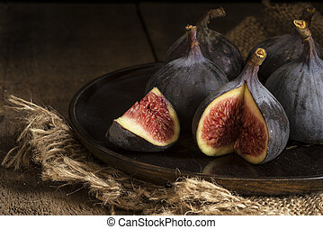 Fresh figs in moody natural lighting set with vintage retro...