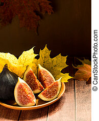 Fresh figs on a plate with yellow autumn leaves wooden rustic background