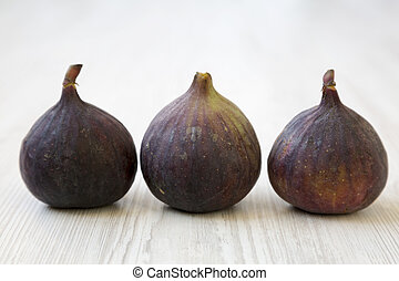 Fresh figs on a white wooden background, side view. Close-up.