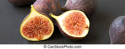 Fresh figs on black surface, side view. Close-up.