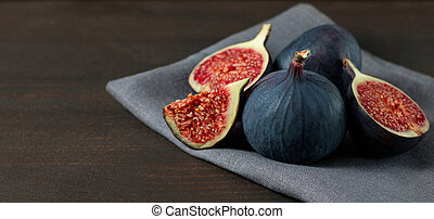 Fresh figs on dark background with copy space. Purple ripe sliced and whole figs on a grey napkin. Side view. Figs on brown wooden background