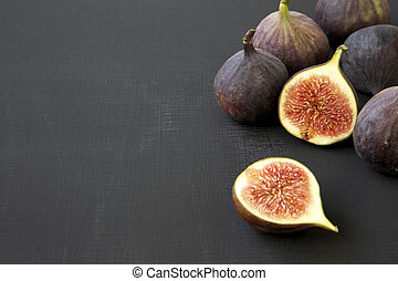Fresh figs on dark surface, side view. Close-up. Copy space and text area.