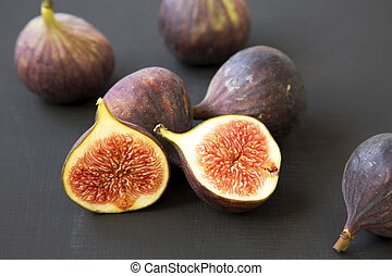 Fresh figs on dark surface, side view. Close-up.
