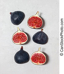 Fresh figs on grey concrete background. Food Photo. Purple figs with red seeds. Flat lay, top view. Food concept