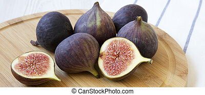 Fresh figs on round bamboo board, side view. Close-up.