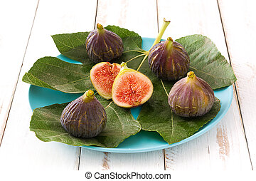 Fresh figs on white wooden background