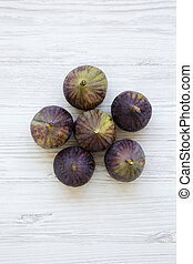 Fresh figs on white wooden table, top view. From above, overhead.