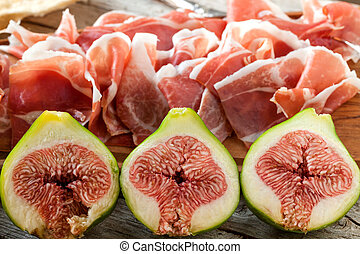 Fresh figs with ham on a white plate