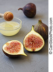 Fresh figs with honey on gray background, side view. Close-up.