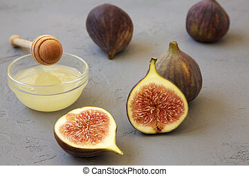 Fresh figs with honey on gray background, side view. Closeup.