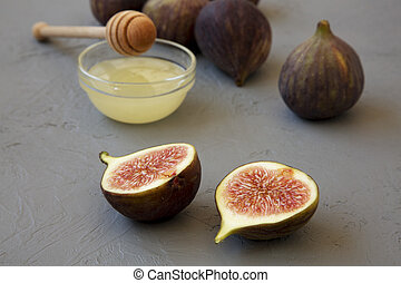 Fresh figs with honey on gray surface, side view. Closeup.