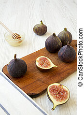 Fresh figs with honey, side view. White wooden table. Close-up.