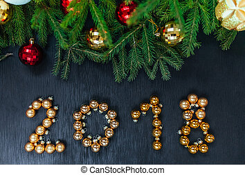 Fresh fir branch with Christmas toys. Beautiful background to insert text. View from the top. Christmas design wooden background. The marbles forming the figures 2018, for the new year.