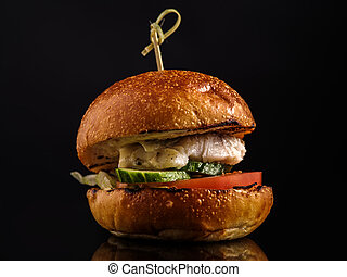 Fresh Fish burger with vegetables on a dark background.