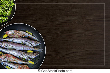 Fresh fish cleaned and prepared for cooking in a frying pan and spinach on a background with frame