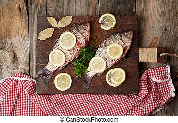 fresh fish in crucian scales on a brown old wooden cutting board