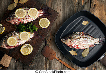 fresh fish in crucian scales on a brown old wooden cutting board, food seasoned with spices