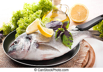 Fresh fish of dorado on a frying pan with a lemon and olive ...