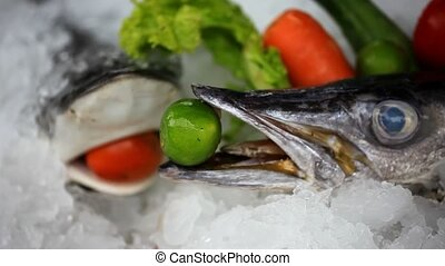 Fresh fish on ice decorated vegetables for sale at market....