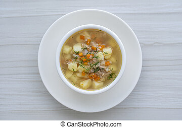 Fresh fish soup with carrots, potatoes and onions in a white plate, close up. Tasty dinner consists of a fish soup with tuna