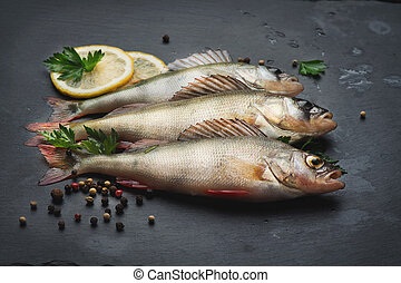 Fresh fish with aromatic herbs, spices, salt. Raw perches on dark slate tray