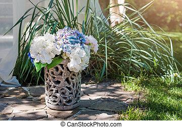 Fresh flowers arrangement in vase in the garden. Decorative bouquet for festive event.