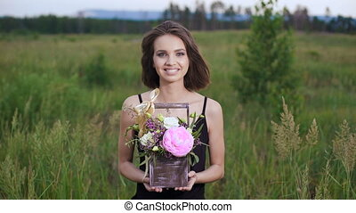 Fresh flowers in a stylish drawer. Beautiful brunette in a flowery field in the evening.